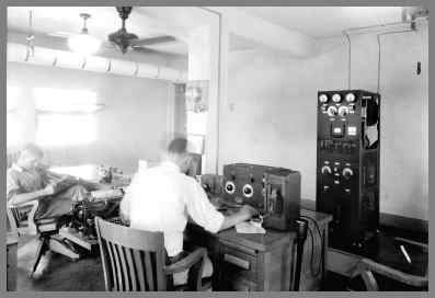 A later WUG2 radio room with transmitter in the background and 2 operators at desks in the foreground.