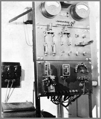 Big open rack with two large meters at the top and a number of knife switches and other gear below