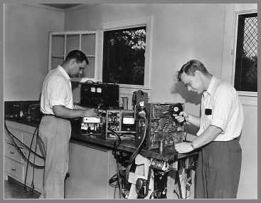 Two men working on two-way radio gear. Measurements Model 80 signal generator on the bench at the rear.