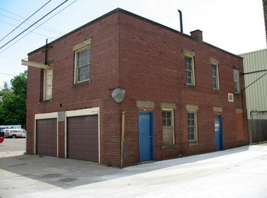 Photo of a 2 story brick building with 2 garage doors on the street side.