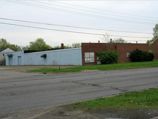 Photo of a medium size single story brick and cinder block building with 2 garage doors at the rear